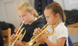 Two school girls playing the trumpet