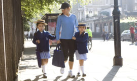 Two young school girls being accompanied by teacher outside